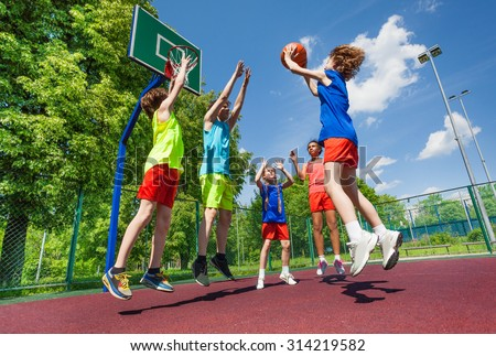 Teens jump for ball during basketball game