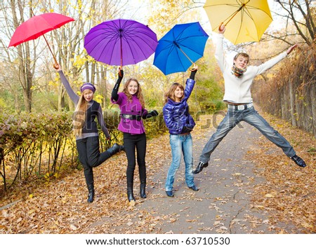 Teens jumping with umbrellas in hands