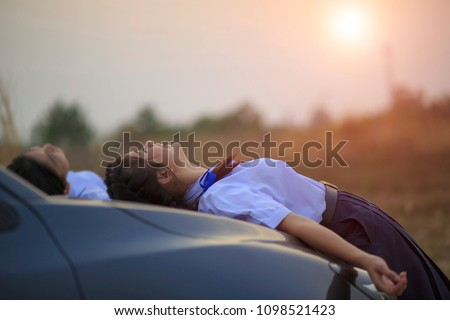 Teens of thai student, relaxing smiling while playing lying on the car enjoying in park at sunset feel relaxed after stress in school classroom. vintage tone, Teenage school friends,Space for text