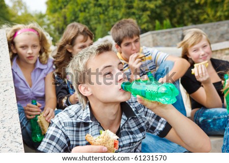 Teens with  sandwiches and soda water