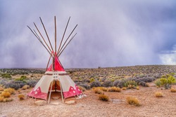 Teepee, Tipi or wigwom, a traditional cone-shape tent used by Indian in North america. Taken from reservation area in Grand Canyon West Rim, Arizona, USA. Heavily raining in the background.