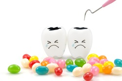 Teeth crying emotion with dental plaque cleaning tool and candy ,isolated on white background, With clipping path teeth and tool
