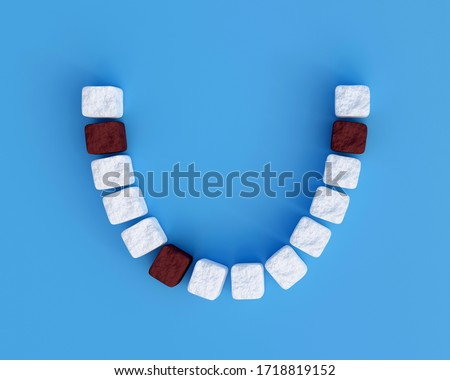 Teeth from sugar cubes on blue background, some brown sugar teeth, concept for sweet tooth, caries. Sugar is the cause of tooth decay. 3d render Stock foto ©