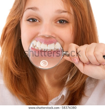 Teeth of young woman through magnifier, isolated on white background.
