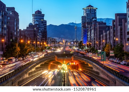 Tehran,Iran,Famous night view of Tehran,Flow of traffic round Tohid Tunnel with Milad Tower and Alborz Mountains in Background, Tohid Tunnel one of longest urban tunnel in Middle East