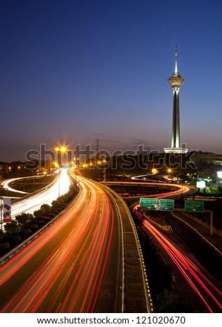 TEHRAN, IRAN - JULY 16: Illuminated Milad Tower and light trails of cars on July 16, 2011 in Tehran, Iran. This is a night shot from streets of Tehran, with its famous Landmark, the Milad Tower.