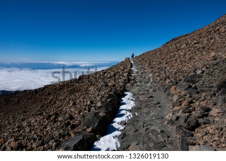 Teide touristic route and rear view of isolated tourist trekking