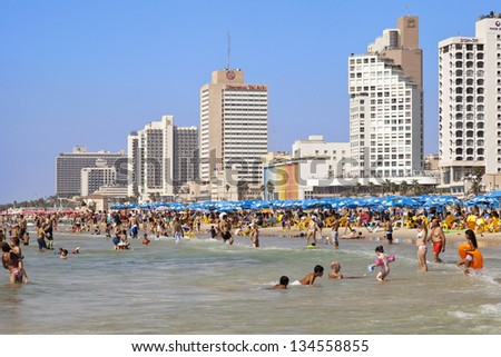 TEL AVIV - AUGUST 18: Beach and hotels strip packed with several people sunbathing, hiding in a parasol\'s shade, or cooling themselves in the ocean. On August 18 2012 in Tel Aviv, Israel.
