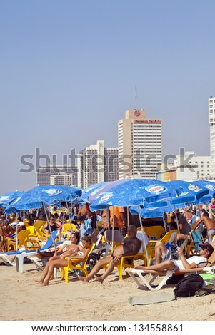 TEL AVIV - AUGUST 18: The Tel Aviv beach and hotels strip, packed with several people either sunbathing or hiding in a parasol\'s shade. On August 18 2012 in Tel Aviv, Israel.