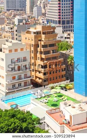 Tel-Aviv close cityscape Top view with blue pool and green open veranda