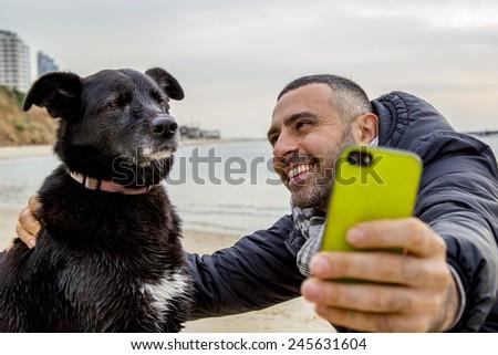 Tel-Aviv - January 19,2014: Man helping his grumpy dog friend to take a social media selfie image using a smartphone