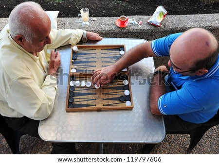 TEL AVIV - NOV 17: Old Israeli men playing backgammon on November 17 2008 in Tel Aviv, Israel.It's one of the oldest board games for two players in the world.