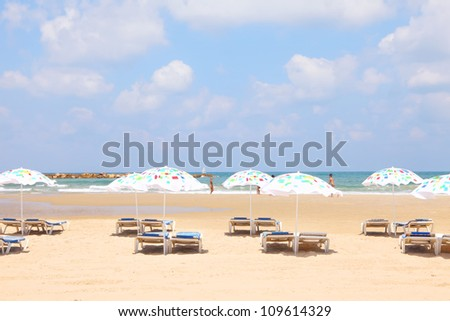 Tel-Aviv sandy beach with colorful umbrellas and lounges (Mediterranean sea. Israel)