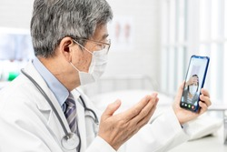 Tele medicine concept -  asian senior male doctor with face mask explain to the patient about the disease by video chat on cell phone in hospital