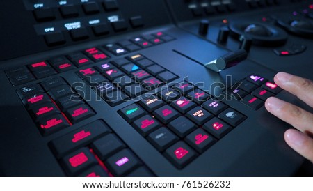 Telecine controller machine and man hand editing or adjusting color on digital video movie or film in the post production stage.