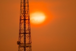 Telecom communication concept, communication construction pole on sihouette sunset on golden sky and cloud background, beautiful sunshine big red sun over hills in twilight for graphic creative design