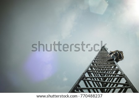 Telecom Worker Climbing Antenna Tower with Tools and Harness #770488237
