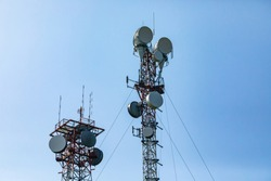 Telecommunication and mobile network infrastructure with two cell site towers side by side, housing antennas and Remote Radio Head, RRH, for greater coverage