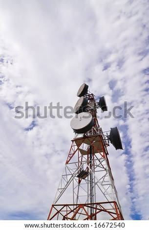 Telecommunication antenna under clouded sky.