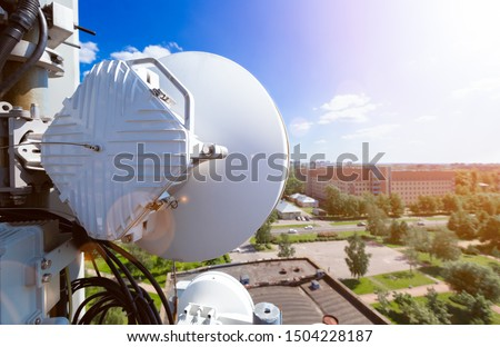 Telecommunication data equipment with microwave radio antennas, outdoor remote radio units, power cables, coaxial cables, optic fibers. Outside part of telecommunication basic station over city #1504228187