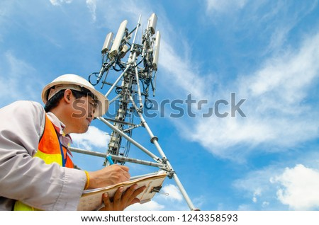 Telecommunication engineer writing on notepad at tower site.Technician record data of maintenance to checklist. #1243358593