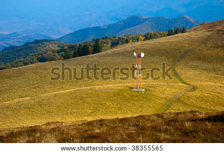 telecommunication gsm antenna on a beautiful mountain meadow pictured in autumn