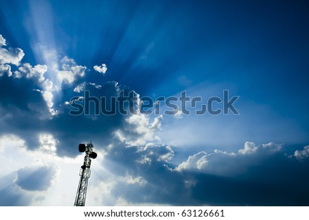 Telecommunication mast / tower with microwave link and TV transmitter antennas over a Beautiful blue sky full with clouds and sun rays.