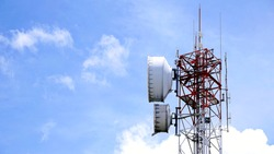 Telecommunication mast with microwave dish transmitter antennas on blue sky background.