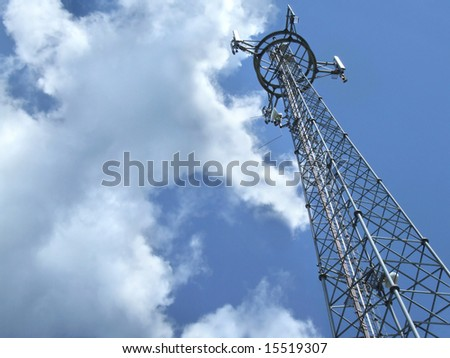 Telecommunication tower - antenna details against cloudy sky.