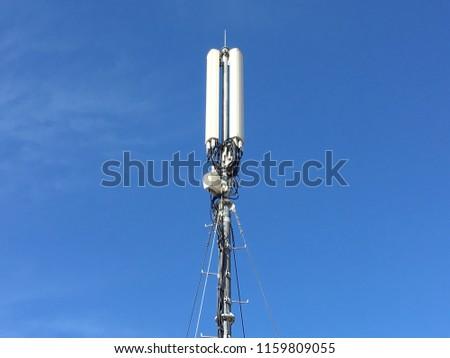 Telecommunication tower. Digital wireless communication system. Basic station mobile phone. 5G of the smart antenna of a basic radiotelephone. - Shutterstock ID 1159809055