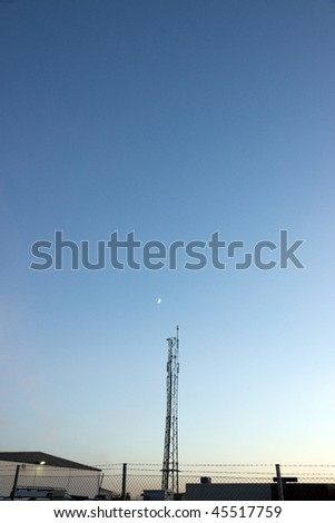 telecommunication tower in an industrial area against evening sky