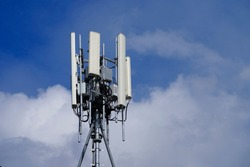 Telecommunication tower of 4G and 5G cellular. Macro Base Station. 5G radio network telecommunication equipment with radio modules and smart antennas mounted on a metal against cloulds sky background.