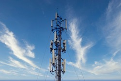 Telecommunication tower of 4G and 5G cellular. Macro Base Station. Wireless Communication Antenna Transmitter. Telecommunication tower with antennas against blue sky and clouds background.