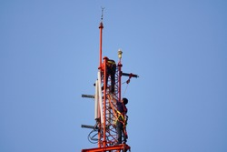 Telecommunication tower of 4G and 5G cellular. radio network telecommunication equipment with radio modules and smart antennas mounted on a metal with engineer working ordinary maintenance and control