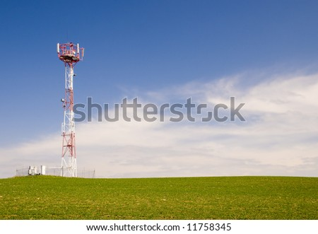 Telecommunication tower on the green field with blue sky
