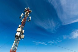 Telecommunication tower or mast with microwave, radio panel antennas, outdoor remote radio units, power cables, coaxial cables, optic fibers are installed on the top mast and blue sky as background