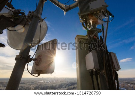Telecommunication tower or mast with microwave, radio panel antennas, outdoor remote radio units, power cables, coaxial cables, optic fibers are on the top mast that located in rural.