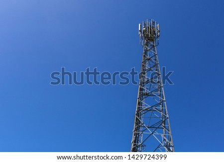 Telecommunication tower or mast with microwave, radio panel antennas, outdoor remote radio units, power cables, coaxial cables, optic fibers are installed on the top mast and blue sky as background #1429724399