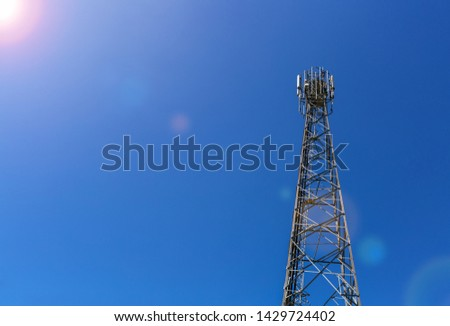 Telecommunication tower or mast with microwave, radio panel antennas, outdoor remote radio units, power cables, coaxial cables, optic fibers are installed on the top mast and sun rays on the sky #1429724402