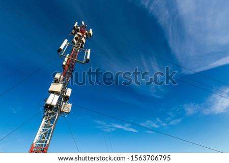 Telecommunication tower or mast with microwave, radio panel antennas, outdoor remote radio units, power cables, coaxial cables, optic fibers are installed on the top mast and blue sky as background #1563706795