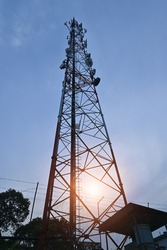 Telecommunication tower with a background of blue and orange clouds at sunset.
