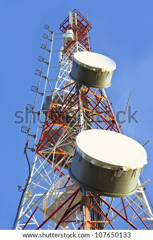Telecommunication tower with antennas a blue sky.