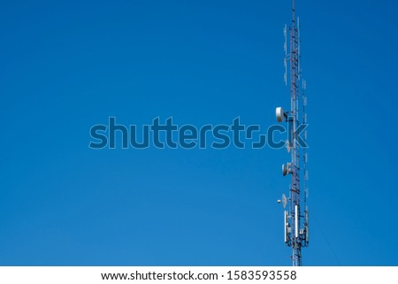 Telecommunication tower with blue sky and white clouds background. Antenna on blue sky. Radio and satellite pole. Communication technology. Telecommunication industry. Mobile or telecom 4g network.
