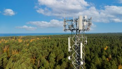 telecommunication tower with cellular antennas for 5g mobile internet network on forest and blue sky background