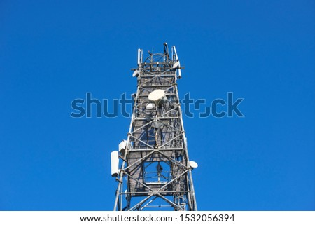Telecommunication tower with clear blue sky background. Antenna on blue sky. Radio and satellite pole. Communication technology. Telecommunication industry. Mobile or telecom 4g and 5g network.
