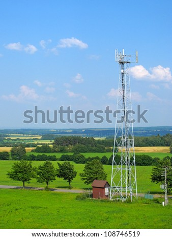 Telecommunication tower with different antenna in natural landscape.