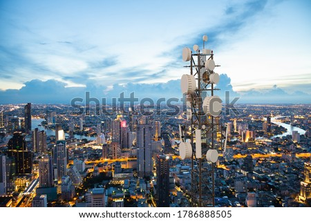 Telecommunication tower with 5G cellular network antenna on night city background