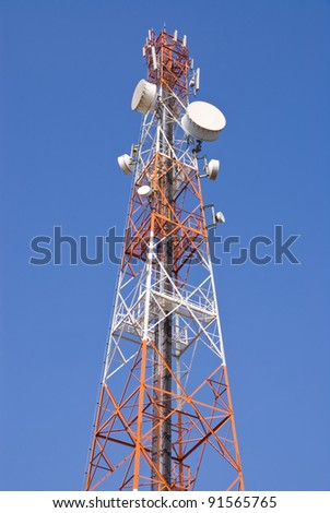 Telecommunication tower with microwave link antennas against blue sky