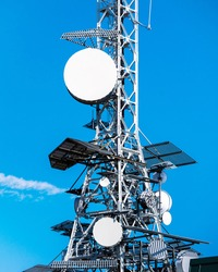 Telecommunication tower with television (TV), broadcasting and 5G antennas with blue sky. Arrival of 5G mobile telephony and problems of electromagnetic radiation and cancer of electromagnetic waves.