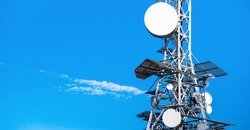 Telecommunication tower with television (TV), satellite, broadcasting and 5G antennas with blue sky for copy space. Problems of electromagnetic radiation and cancer of electromagnetic waves with 5G.